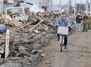 homem pedala após o terremoto de 11/03/2011, no japão