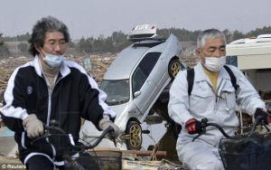 homens pedalam e m natori, miyagi, japão, após o terremoto de 2011.