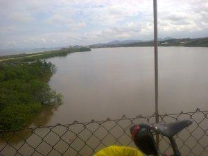 típica foto de viagem em solitário. aparecem a bicicleta e a paisagem. nesse caso, foto tirada de cima da ponte pênsil sobre a lagoa de barra-velha, em santa catarina.