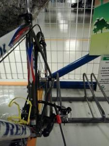 passando a u-lock pela roda e pelos chain stays, com o cabo auxiliar prendendo a roda dianteira.