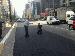 o motorista atropelador xingando o ciclista atropelado, que ainda não conseguira levantar-se.
