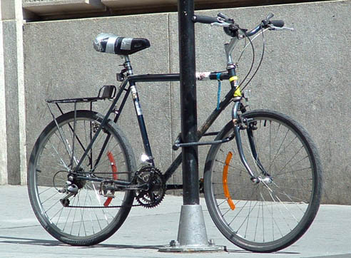 presa no poste. espero que a roda traseira tenha blocagem anti-furto...  mas um selim confortável e remendado com silver-tape quem furtará?