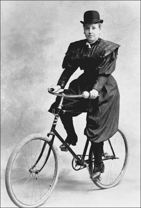 1895. mulher em bicicleta com quadro diamante, que força-a a usar uma vestimenta que já aponta par ao uso das calças pelas mulheres. um escândalo na época.