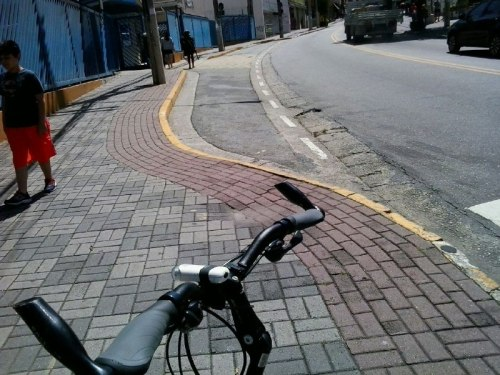 exemplo de uso de bloquetes vermelhos na Av Tucurvi, para desenho em calçada. Não é ciclovia, é arremate de calçada.