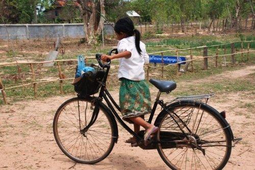 menina pedalando bicicleta grande demais para ela.